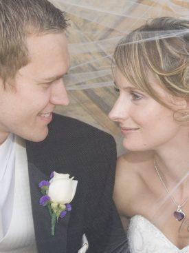Poročni par pod pajčolanom